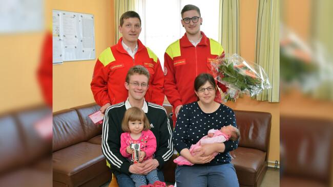 Auf der ASBÖ-Dienststelle wurden kleine Geschenke ausgetauscht: Kathrin Prammer mit der kleinen Annalena und Vater Richard Sauprügl mit den beiden Sanitätern Manfred Hößl und Mathias Aigelsreiter.