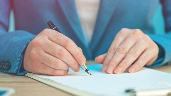 Symbolbild Frau Schreiben Unterschrift Liste Blatt