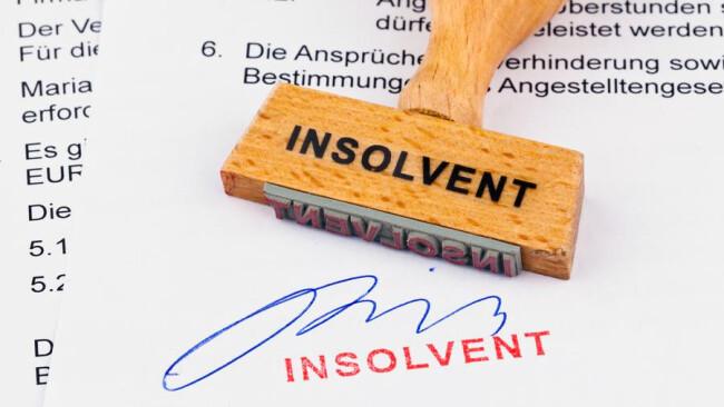 Holzstempel auf Dokument: Insolvenz Ein Stempel aus Holz liegt auf einem Dokument Insolvent