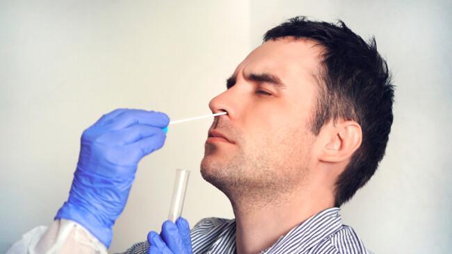 Corona-Test Nasenbohrer Coronavirus Symbolbild