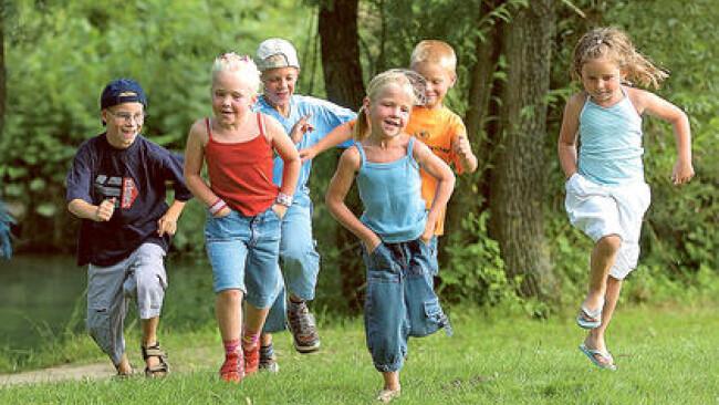 Kinder laufen ueber eine Wiese
